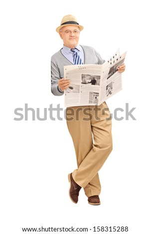 Full length portrait of a senior gentleman holding a newspaper and leaning against a wall - stock photo