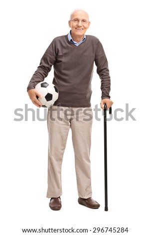 Full length portrait of a senior gentleman with a cane holding a football and looking at the camera isolated on white background