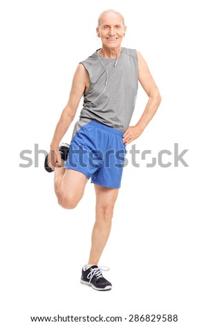 Full length portrait of a senior in sportswear stretching his leg and listening music on headphones isolated on white background - stock photo