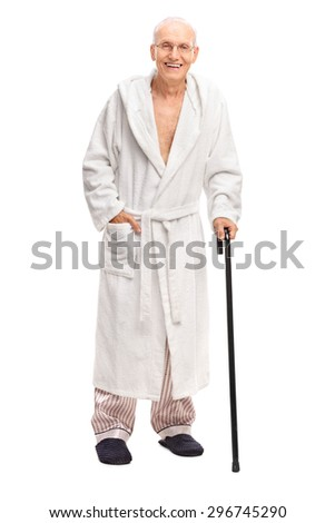 Full length portrait of a senior man in a bathrobe holding a cane and looking at the camera isolated on white background - stock photo