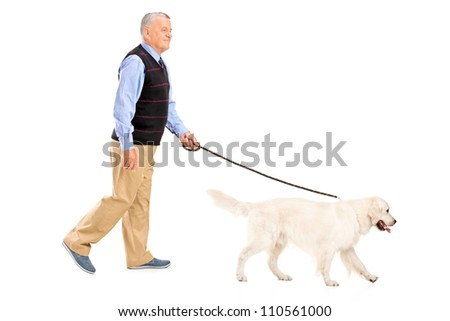 Full length portrait of a senior man walking a dog, isolated on white background