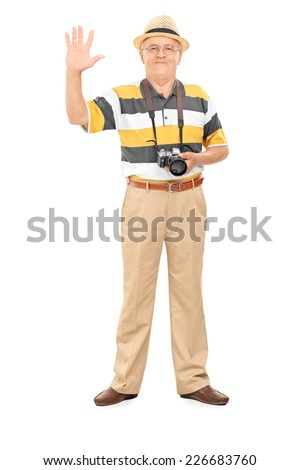 Full length portrait of a senior photographer waving with hand isolated on white background - stock photo