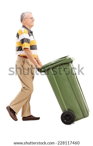 Full length portrait of a senior pushing a large green trash can isolated on white background - stock photo