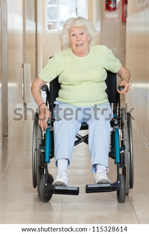 Full length portrait of a senior woman sitting in a wheel chair - stock photo