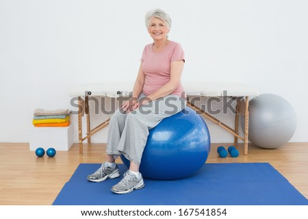 Full length portrait of a senior woman sitting on fitness ball in the hospital gym - stock photo