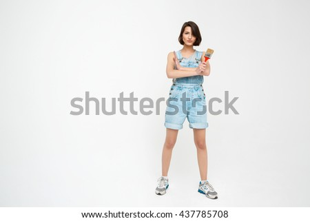Full length portrait of a seriously pretty girl, in gray shirt and denim overall with crossed hands, holding painting brush, isolated on white background - stock photo