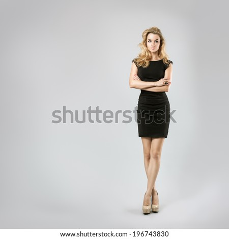 Full Length Portrait of a Sexy Blonde Woman in Little Black Dress. Crossed Arms and Legs. Closed Body Posture. Body Language Concept. - stock photo