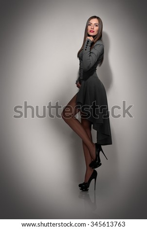 Full Length Portrait of a Sexy Woman in Little Black Fashion Dress on dark grey background with shadow