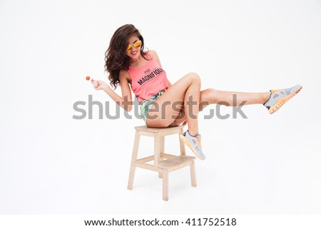 Full length portrait of a sexy woman in sunglasses and candy posing on the chair isolated on a white background - stock photo