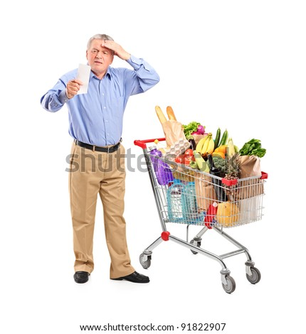 Full length portrait of a shocked senior looking at store receipt next to a shopping cart isolated on white background - stock photo