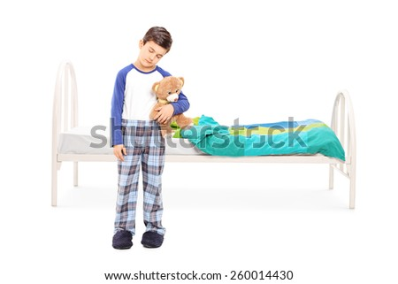 Full length portrait of a sleepy boy standing in front of a bed isolated on white background - stock photo