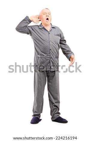 Full length portrait of a sleepy senior in pajamas stretching on white background - stock photo