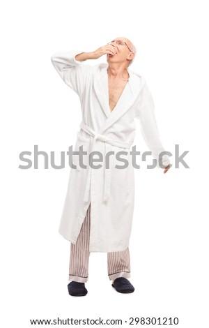 Full length portrait of a sleepy senior man in a white bathrobe yawning isolated on white background - stock photo
