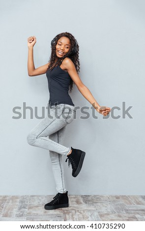 Full length portrait of a smiling afro american woman posing in headphones over gray background - stock photo