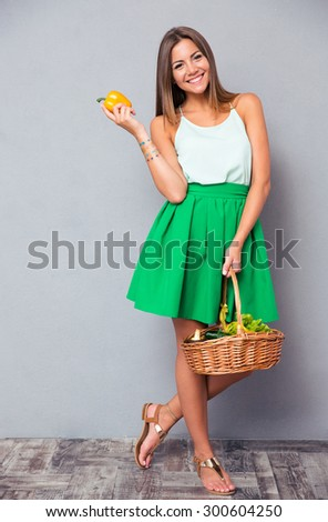 Full length portrait of a smiling attractive woman holding basket with vegetables over gray background - stock photo