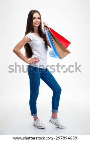 Full length portrait of a smiling attractive woman holding shopping bags isolated on a white background - stock photo