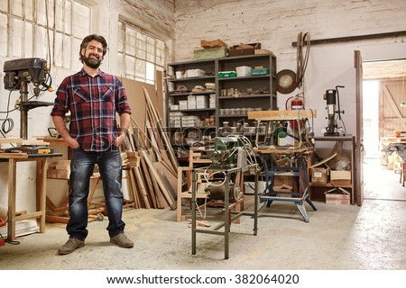 Full length portrait of a smiling bearded crafstman, standing proudly in his workshop, with heavy-duty machinery for woodwork - stock photo