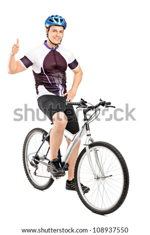 Full length portrait of a smiling bicyclist posing on a bicycle and giving a thumb up isolated on white background