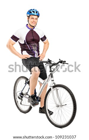 Full length portrait of a smiling bicyclist posing on a bicycle isolated against white background