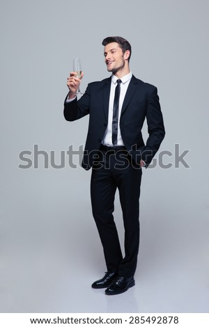 Full length portrait of a smiling businessman holding glass of champagne over gray background and looking at camera - stock photo