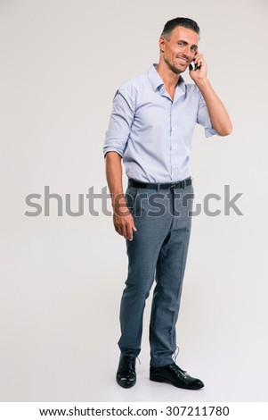 Full length portrait of a smiling businessman talking on the phone isolated on a white  - stock photo