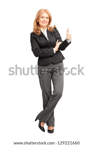 Full length portrait of a smiling businesswoman leaning on wall and giving a thumb up isolated on white background - stock photo