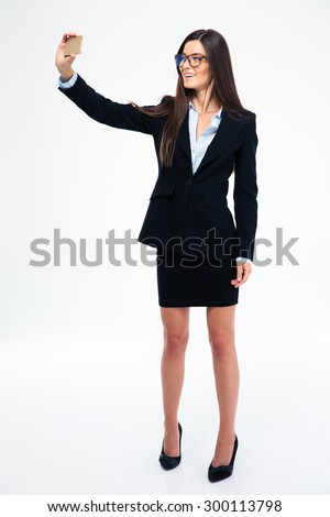 Full length portrait of a smiling businesswoman making selfie photo on smartphone isolated on a white background - stock photo