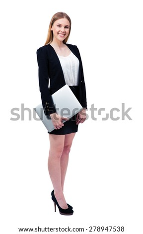 Full length portrait of a smiling businesswoman standing with laptop over white background and looking at camera - stock photo