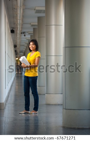 Full length portrait of a smiling college student wearing yellow shirt standing holding books in a modern campus hallway. Female Asian Thai late teens, early 20s of Chinese descent looking at camera
