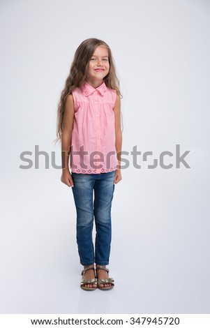 Full length portrait of a smiling cute little girl standing isolated on a white background - stock photo
