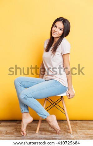 Full length portrait of a smiling cute woman sitting on the chair over yellow background - stock photo