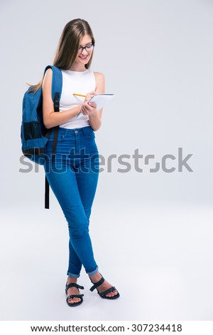 Full length portrait of a smiling female teenager writing notes in notebook isolated on a white background - stock photo
