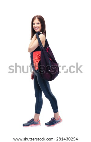 Full length portrait of a smiling fitness woman standing with sports bag isolated on a white background. Looking at camera - stock photo