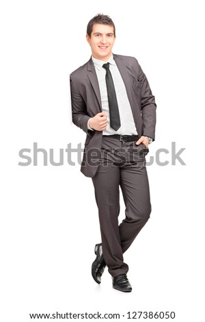 Full length portrait of a smiling male businessman leaning against wall isolated on white background - stock photo