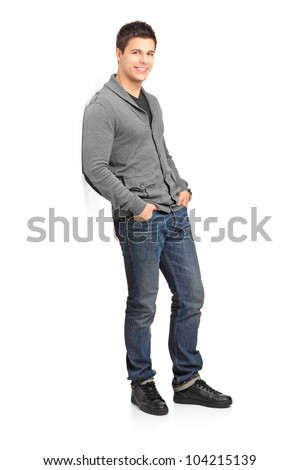 Full length portrait of a smiling male leaning against wall isolated on white background