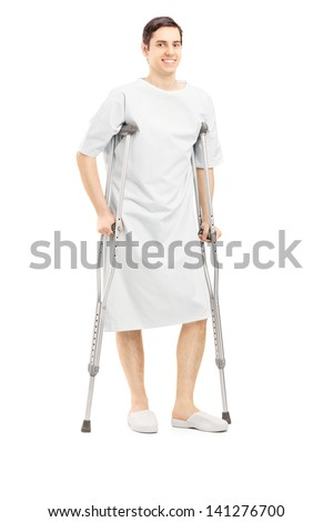 Full length portrait of a smiling male patient in hospital gown with crutches isolated on white background
