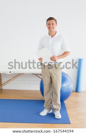 Full length portrait of a smiling male trainer with clipboard in the gym at hospital