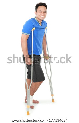 Full length portrait of a smiling male with broken foot using crutch isolated on white background - stock photo