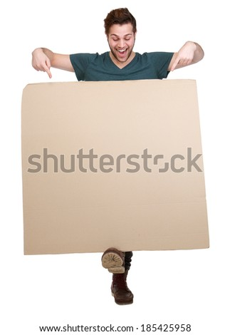 Full length portrait of a smiling man pointing fingers down to blank poster board on isolated white background - stock photo