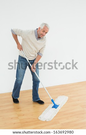 Full length portrait of a smiling mature man mopping the floor in a room