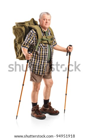 Full length portrait of a smiling mature with backpack holding hiking poles posing isolated on white background - stock photo