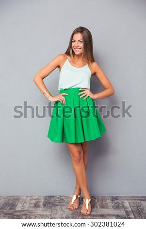 Full length portrait of a smiling pretty woman standing on gray background. Looking at camera - stock photo