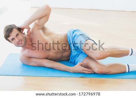 Full length portrait of a smiling shirtless young man exercising in fitness studio
