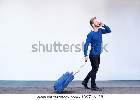 Full length portrait of a smiling travel man walking with suitcase and talking on mobile phone  - stock photo