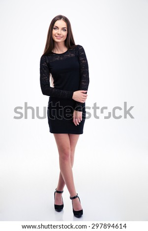 Full length portrait of a smiling trendy woman in black dress standing isolated on a white background. Looking at camera - stock photo