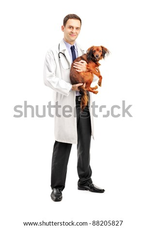Full length portrait of a smiling veterinarian holding a puppy isolated on white background