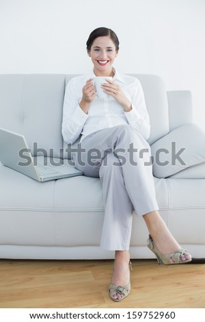 Full length portrait of a smiling well dressed young woman with laptop and coffee cup on sofa at home - stock photo