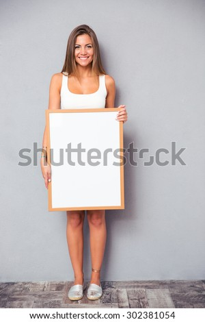 Full length portrait of a smiling woman holding blank board on gray background - stock photo