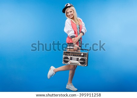 Full length portrait of a smiling woman holding retro boom box on blue background - stock photo
