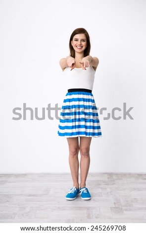 Full length portrait of a smiling woman pointing at camera - stock photo